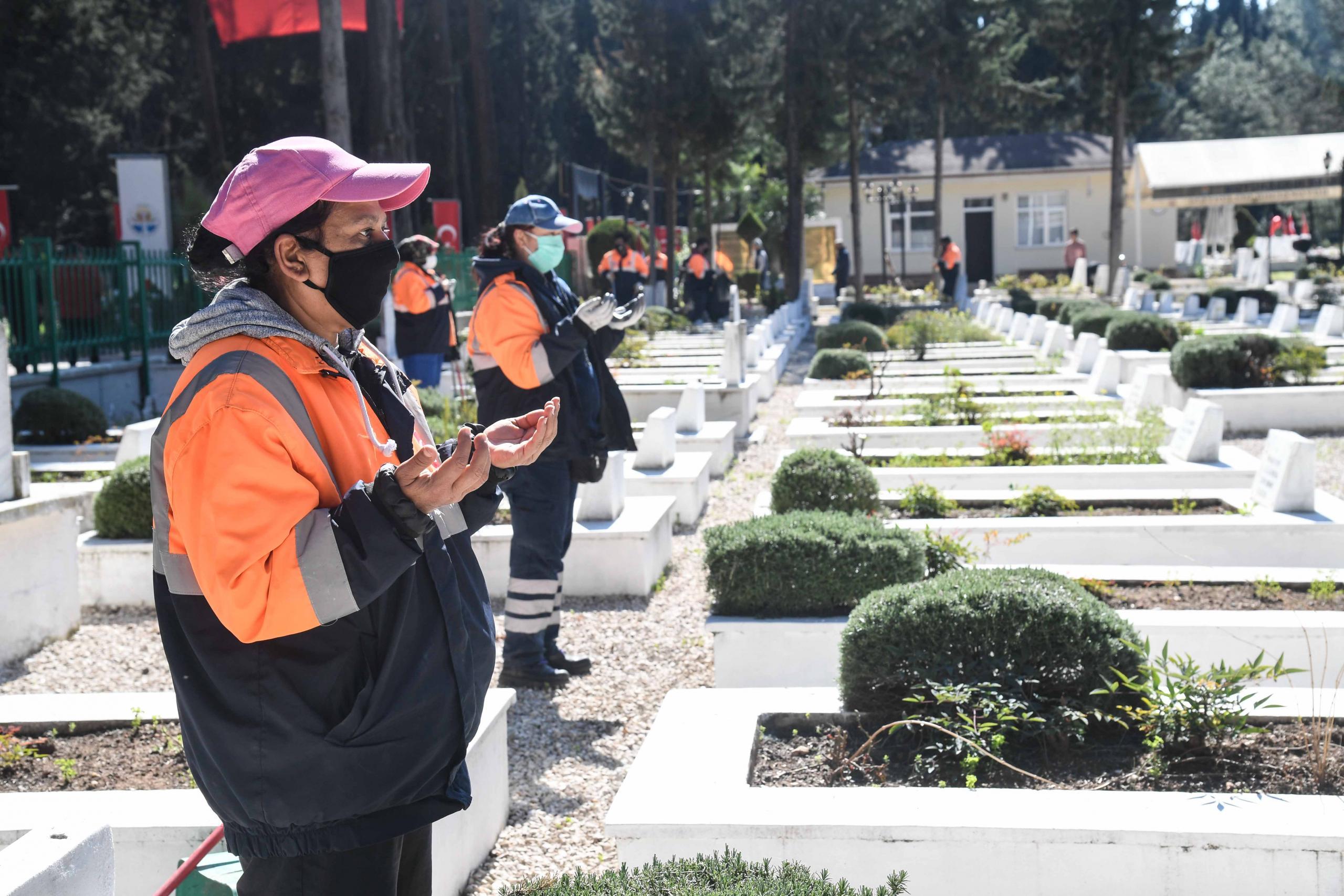 Mezarlıklarda temizlik yapan işçiler, şehitlikteki çalışmalarının ardından dua okudu.